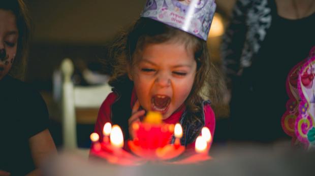Ein Kind vor einem Geburtstagskuchen